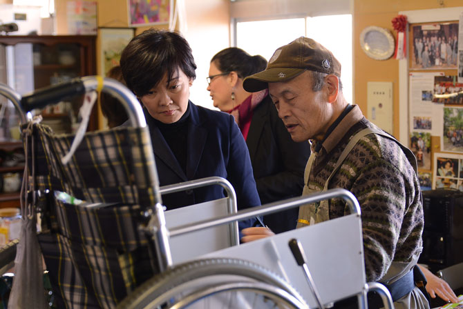 Akie Abe works with a volunteer to fix a wheelchair for Cambodia